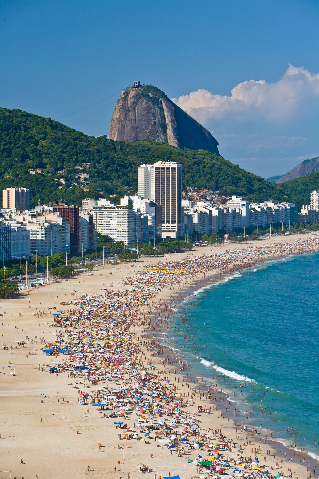 Aerial view of Copacabana Beach full of beachgoers, showing Sugar Loaf Mountain in the background, Rio de Janeiro, Brazil. Copacabana is the most famous beach in Rio