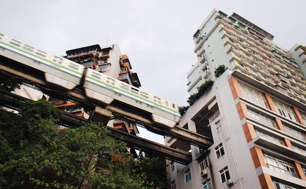 July 31, 2014, Chongqing. A light trail train passing through a residential building in Chongqing.